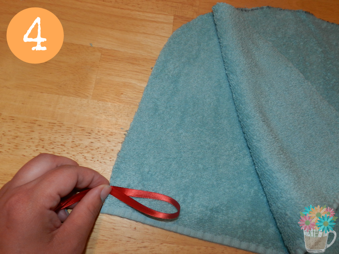 Step 4: Fold a strip of ribbon into a loop that is 2 to 3 inches long and position it in between the two layers of towel as illustrated above, about 1/2 inch from the finished edge.
